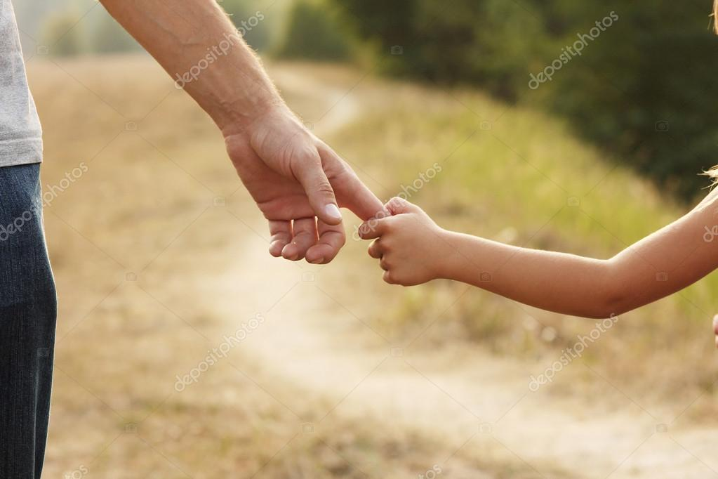 Parent holds hand of child