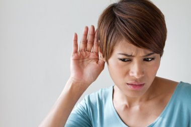 woman suffers from hearing impairment, hard of hearing, hearing impair