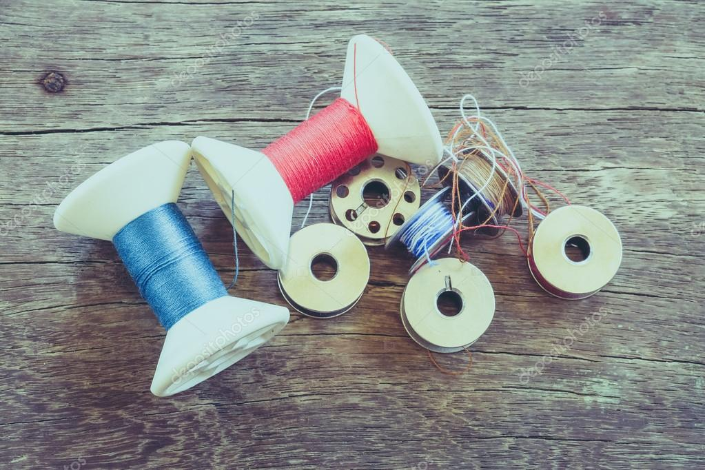 thread rolls on wood background with filter effect retro vintage