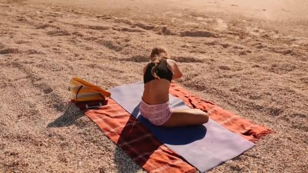 Frau übt sich im Yoga, dehnt sich auf Matte am Strand