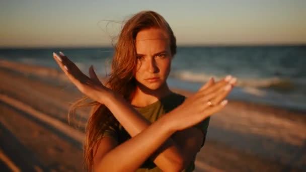 Vážná mladá žena ukazuje zkřížené ruce gesto a při pohledu na pláž moře slunce