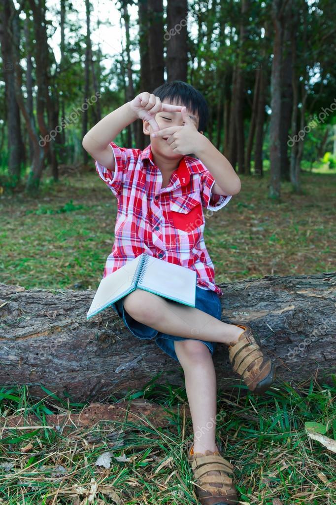 asiatico lo marco con las manos y sonriendo sobre tronco de madera ...