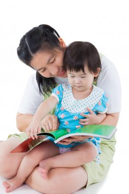 Young female with little asian girl reading a book