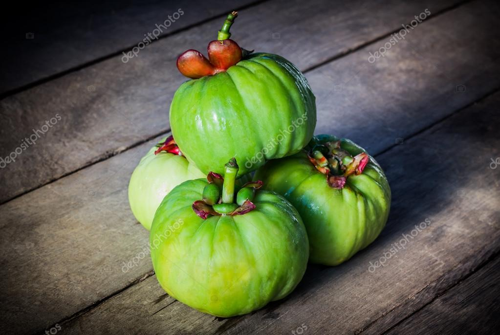 Still life with fresh garcinia cambogia on wooden background (Th