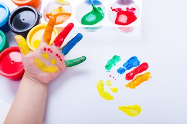 Child paint her palm with smiling face various colors. Studio sh