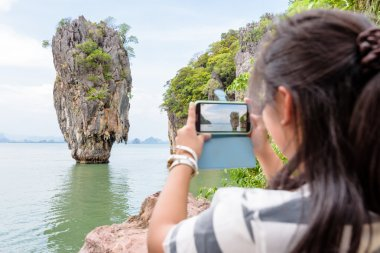 Female traveler shooting natural view by mobile phone
