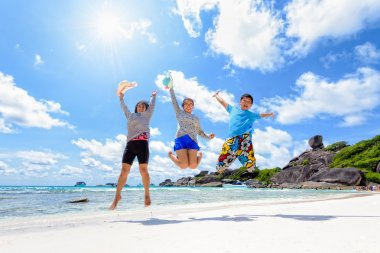 Happy family jumping on beach in Thailand