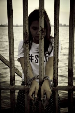 Stock Photo Stock Photo: Rusty chains, shackles binding the hands of a pretty young woman is tied to the iron and arrested.