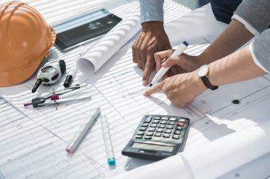 Hands of engineers making corrections in blueprint stock vector
