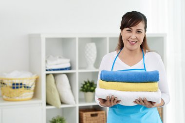 Housewife holding fresh towels
