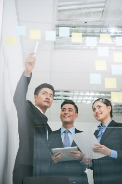 Businessman pointing at stickers on glass wall