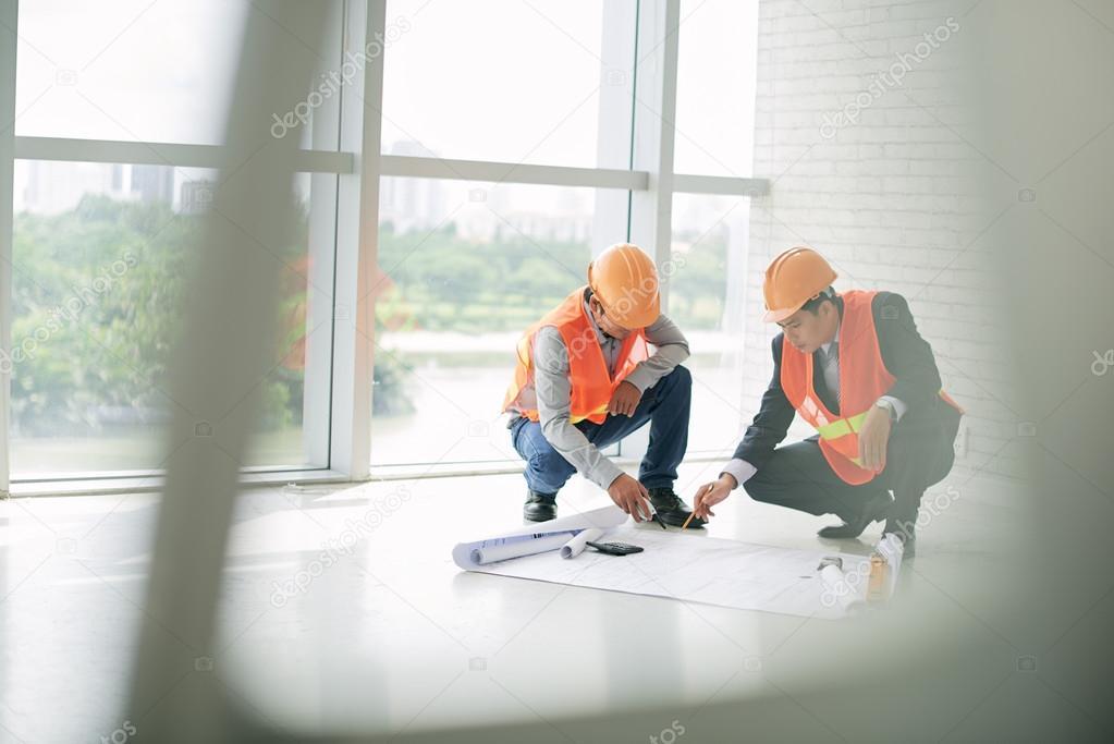 Civil engineers discussing blueprint