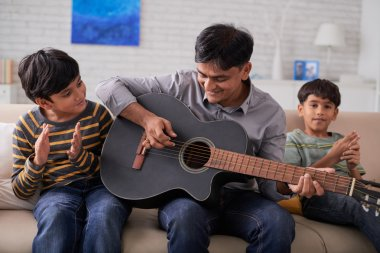 Father playing guitar and sons singing
