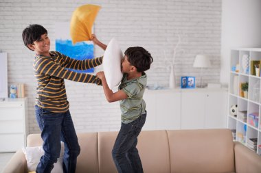 brothers fighting with pillows