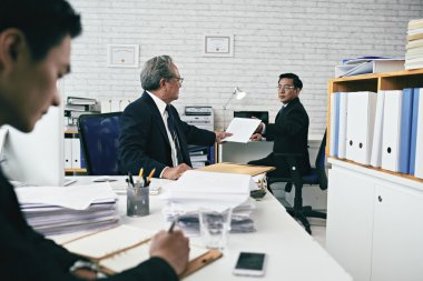 Attorney giving important document to coworker