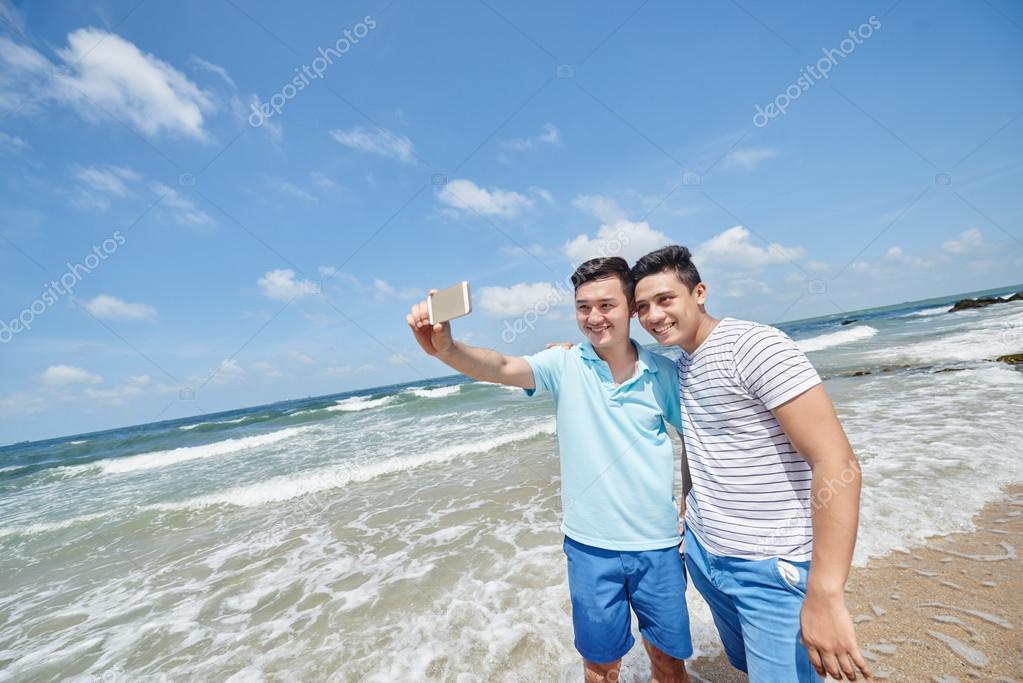 guys taking selfie on beach