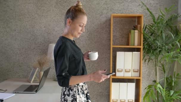 Blokkolása szőke kaukázusi üzletasszony áll az irodában támaszkodik az asztalra, iszik kávét fehér csésze és okostelefon használata