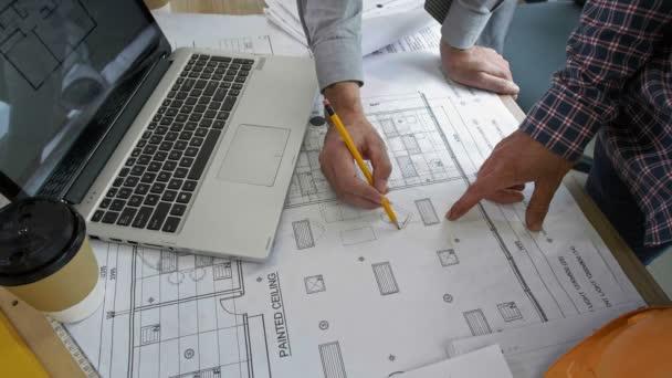 Přímo nad pohledem na plán budovy ležící na stole a mužské ruce ukazuje na něj a dělá si poznámky pomocí tužky