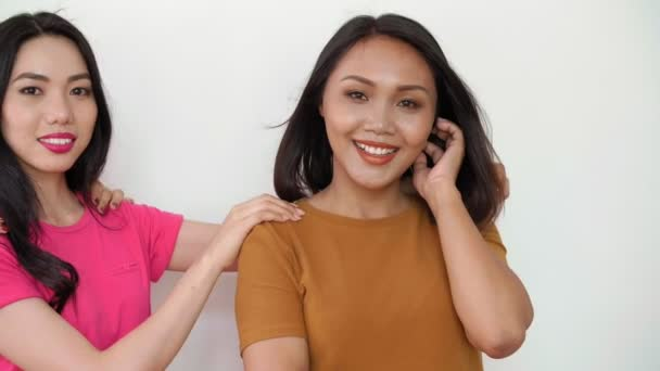 Links drei junge asiatische Frauen, die zusammen stehen, in die Kamera schauen und vor weißem Hintergrund lächeln