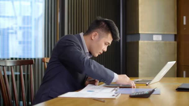 Lockdown of Asian businessman sitting at desktop and working with charts and gadgets