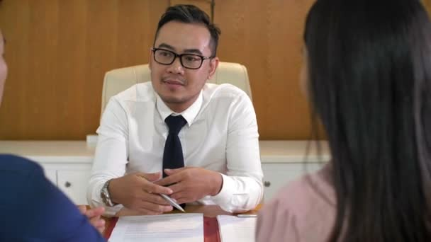 Rare view of middle-aged Asian man in office wear sitting at desktop and consulting Asian family couple sitting in front of him
