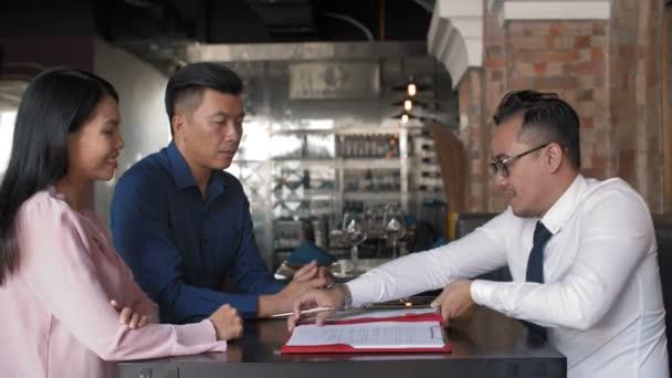 Aussperrung von drei asiatischen Geschäftspartnern bei Vertragsunterzeichnung