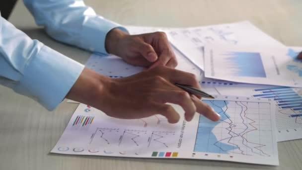 Nahaufnahme des Geschäftsmannes und seiner Kollegin, wie sie die Unternehmensstrategie anhand von Diagrammen auf dem Desktop diskutieren