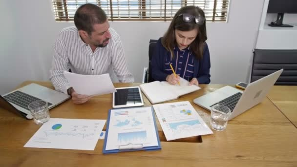 Pan shot of businessman and businesswoman sitting at desk in front of laptops, man holding papers in hands and woman writing something with pencil in notebook