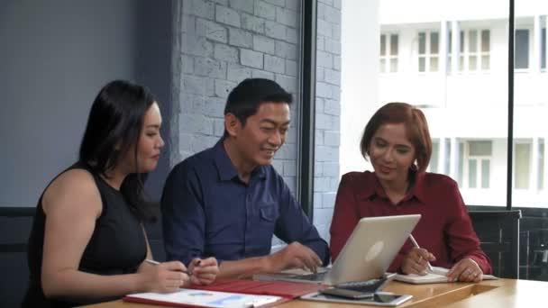 Közepes felvétel ázsiai és férfi munkatársakról, akik együtt ülnek az asztalnál. A férfi a számítógép képernyőjét nézi, a nők fontos információkat írnak le az újságokba.