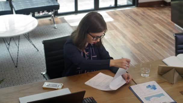 High angle view of Caucasian business lady sitting at desk, reading and then signing contract