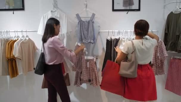 Zadní pohled na mladé trendy asijské ženy a její přítelkyně hledá krásné letní oblečení v módní butik během prodeje sezóny
