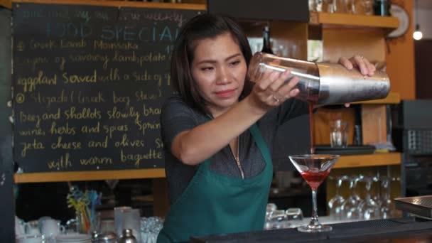 Profesionální asijské žena barman nalévání alkoholický koktejl z třepačky do skla a zdobení s citrónem, zatímco stojí u baru pultu