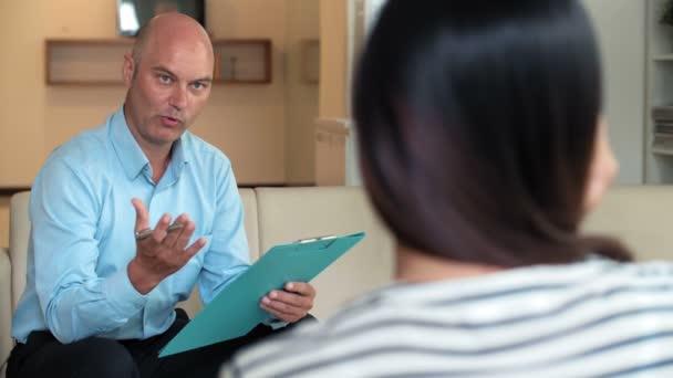 Erfahrener kaukasischer Psychologe mittleren Alters stellt unkenntlich machenden Frauen Fragen zu ihrem Zustand und notiert sich Notizen auf Klemmbrett