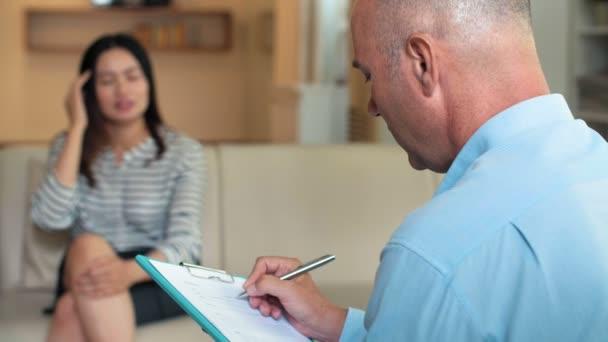 Professionelle männliche Psychotherapeutin mittleren Alters macht medizinische Notizen auf Klemmbrett, während sie einer defokussierten Asiatin auf dem Sofa zuhört