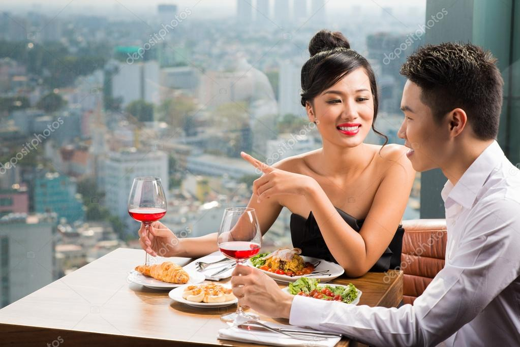 Young Asian couple having dinner in a luxurious restaurant — Photo by  DragonImages