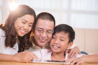 Asian family using digital tablet