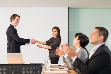 Businessman congratulating Vietnamese manager, her colleagues applauding stock vector