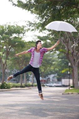 Asian man jumping with umbrella