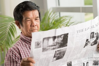 Vietnamese man reading newspaper