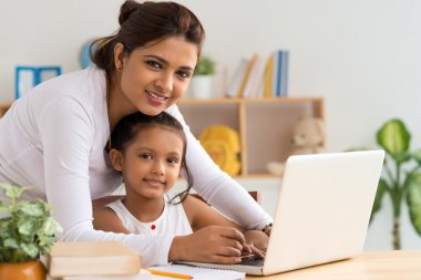 Mother and daughter working on laptop stock vector