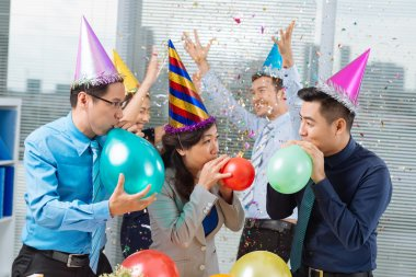 Business colleagues blowing up balloons