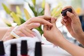Kosmetička, pokrývající nehty odběratele