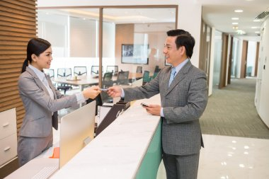 Receptionist giving  card to the businessman