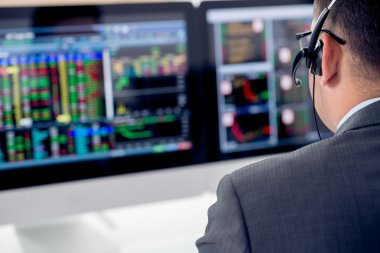 Businessman in headset looking at statistics