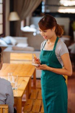 Waitress taking order from her customer in a restaurant stock vector
