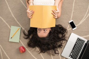 woman covering her face with notebook