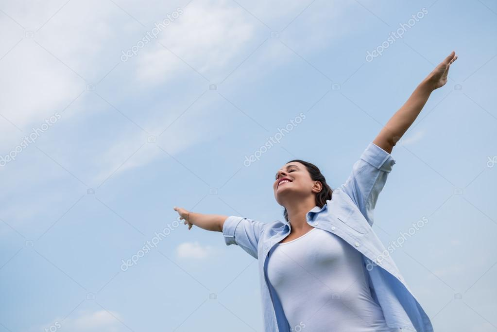 Woman standing outdoors with closed eyes