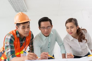 Architects and contractor discussing blueprint