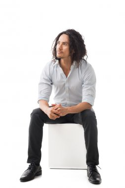 man sitting on white cube