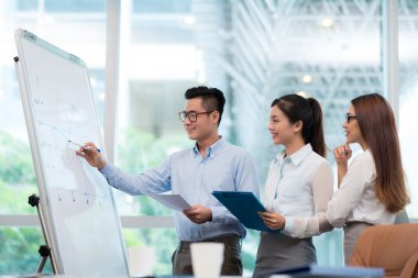 Young Vietnamese businessman explaining chart on the whiteboard to his colleagues stock vector